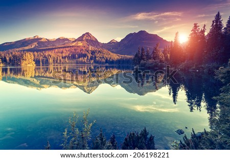 Fantastic mountain lake in National Park High Tatra. Dramatic overcast sky. Strbske pleso, Slovakia, Europe. Beauty world. Retro style filter. Instagram toning effect. - stock photo
