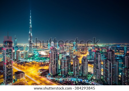 Fantastic nighttime skyline with illuminated skyscrapers. Rooftop perspective of downtown Dubai, UAE.  - stock photo