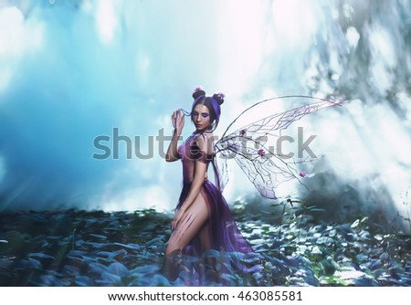 Fantastic photo shoot with smoke. Fairy Coquette walking in the fog. Background fairy forest. Unusual fabulous looks, purple dress and torn wings. Fancy toning.
