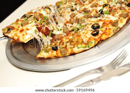 Fantastic pizza, great cheese, fork and knife, serving in restaurant - stock photo