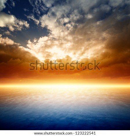Fantastic red sunset, bright light from horizon - stock photo