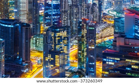 Fantastic rooftop view of a big modern city architecture at night with roads. Business bay, Dubai, United Arab Emirates. - stock photo