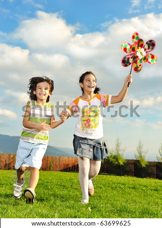 Fantastic scene of happy children running and playing care freely on green meadow in nature - stock photo