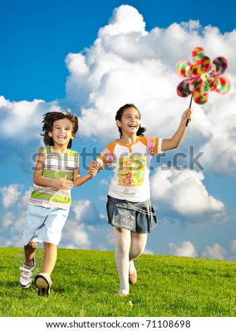 Fantastic scene of happy children running and playing carefreely on green meadow in nature - stock photo