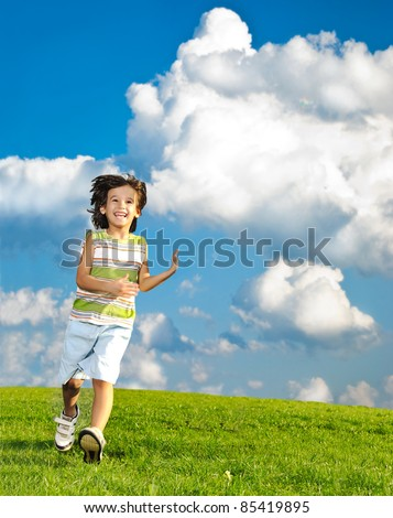 Fantastic scene of happy children running and playing on green meadow in nature, limitless freedom - stock photo