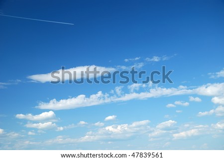 Fantastic soft white clouds against blue sky and far flying airplane - stock photo