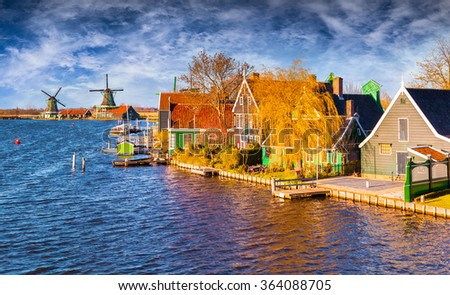 Fantastic spring view of Dutch architecture on the water channel in Zaanstad village. Zaanse Schans Windmills and famous Netherlands canals, Europe.
