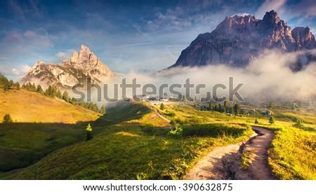 Fantastic summer landscape in Dolomite Alps. Tofane mountain range and Sass de Stria peak in morning mist. View from Falzarego pass.Cortina d'Ampezzo location, Province of Belluno, Italy, Europe. - stock photo