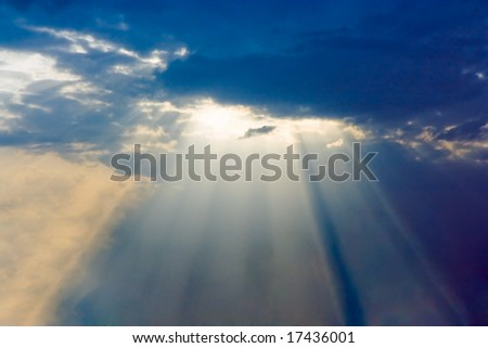 Fantastic sun rays are striking through the clouds like an explosion - stock photo