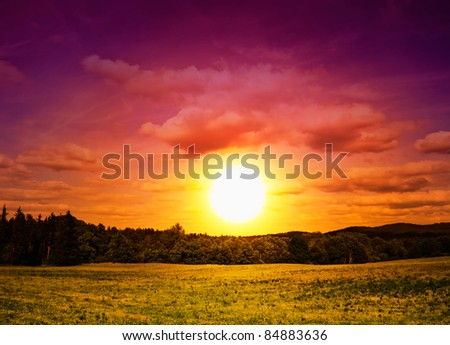 Fantastic Sunset above green meadow - stock photo