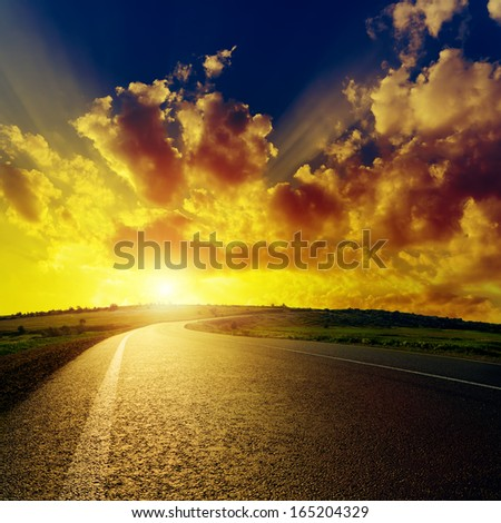 fantastic sunset over asphalt road - stock photo