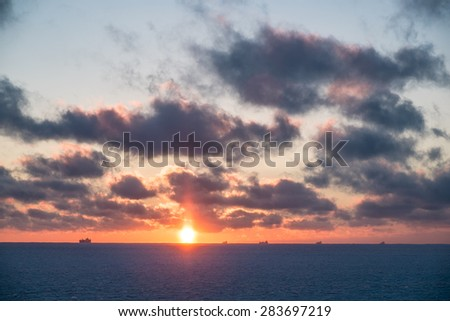 Fantastic view of frozen sea and clouds in winter. Winter sunrise background. The sun comes over the horizon. Beautiful ocean landscape. - stock photo
