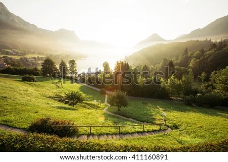 Fantastic views of the morning green garden that glows under sunlight. Dramatic scene. Location: resort Grundlsee, Liezen District of Styria, Austria, Alps. Europe. Beauty world. Instagram effect. - stock photo