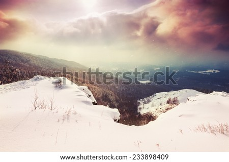 Fantastic winter landscape at sunset. Beautiful snow covered mountains. Winter forest. Retro style filter - stock photo