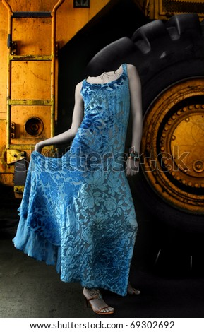 Fantastical fashion portrait of a female model as headless greek statue in blue iridescent dress against industrial equipment background - stock photo