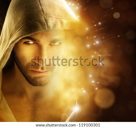 Fantastical portrait of a handsome hero type man in hooded garment in dazzling background with rays of light - stock photo