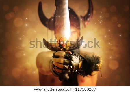 Fantastical portrait of a warrior with focus on powerful sword with skull against magical background of rays of light - stock photo