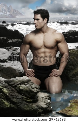 Fantastical portrait of young shirtless body builder on beach with scenic surroundings - stock photo