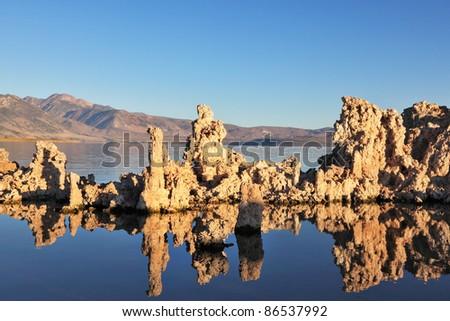 Fantastically beautiful landscape. Mono Lake at sunset. Lake Tufa stalagmites reflected in the smooth waters of lake - stock photo