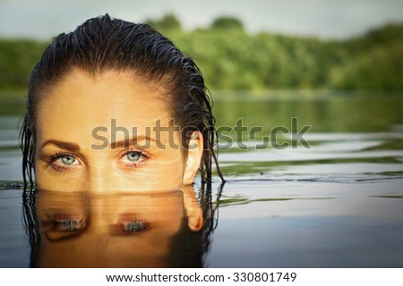 fantasy beautiful woman in the water. looking at the camera.  - stock photo