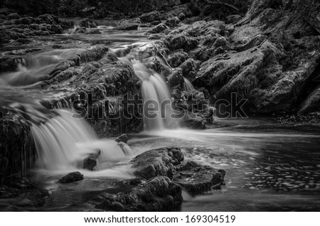 fantasy cascades on mountain river of black and white - stock photo