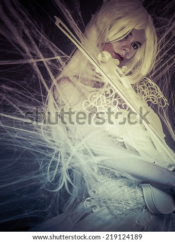 Fantasy concept, sensual young woman with vintage white violin