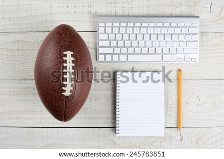 Fantasy Football Draft still life. A computer keyboard, pad and pencil and an American style football on a white wood table in a home office. - stock photo