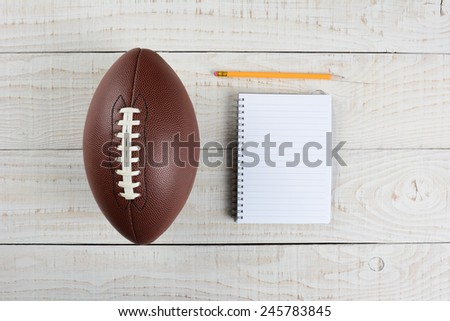 Fantasy Football Draft still life. A pad and pencil and an American style football on a white wood table in a home office. - stock photo