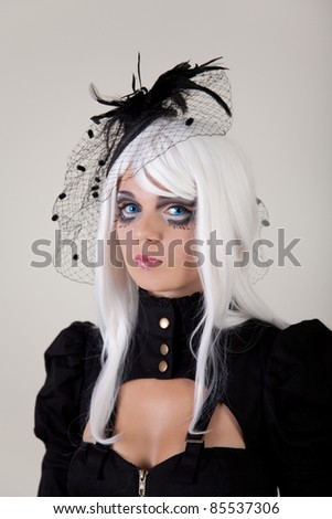 Fantasy girl with creative make-up and blue contact lenses, studio shot - stock photo