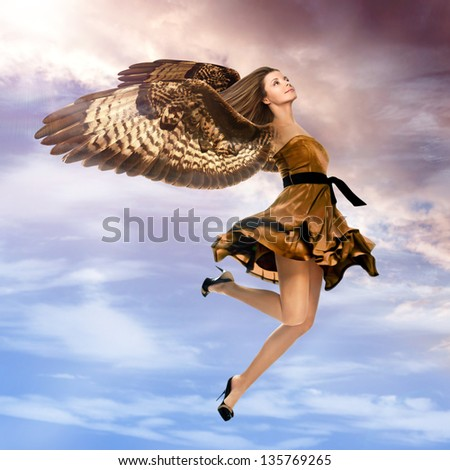 Fantasy girl with falcon wings flying in the stom sky - stock photo