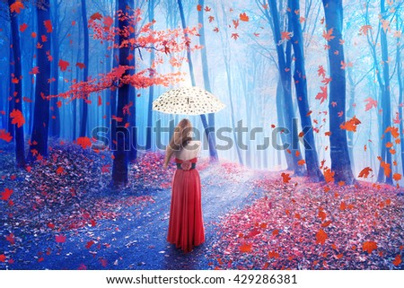 Fantasy image of a beautiful lonely young woman with umbrella walking in a forest in fairy and dreamy realm. Nature background  - stock photo