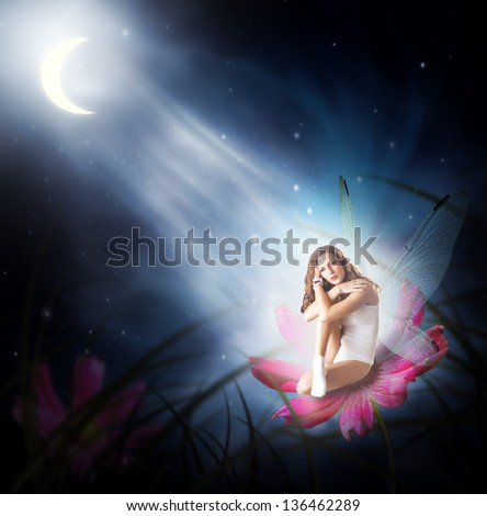 Fantasy. Magical young woman as  fairy with wings sitting on flower in moon light - stock photo