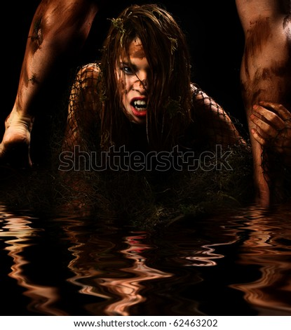 Fantasy monster portrait of couple covered in mud in water. - stock photo