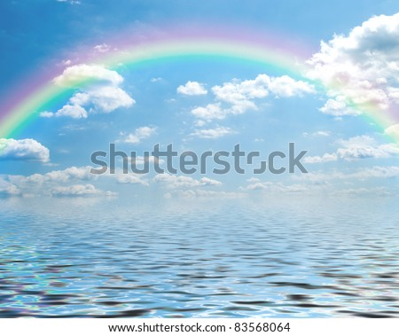 Fantasy of a blue sky and rainbow with cumulus clouds, reflected over water. - stock photo