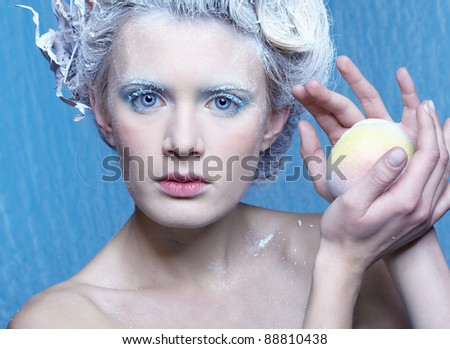 fantasy portrait of beautiful young woman imaging ice fairy on frozen blue with apple - stock photo