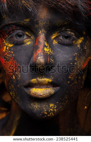 Fantasy portrait of beauty woman. Face art and body art. Red and yellow paint on face. Black skin girl on yellow background - stock photo