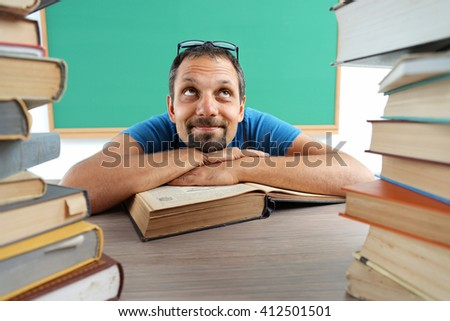 Fantasy pupil looking up as if daydreaming or thinking of something pleasant while sitting at the desk with open book. Photos adult student, creative concept with Back to school theme - stock photo