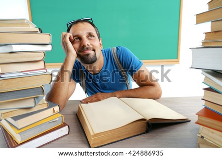 Fantasy teacher looking up as if daydreaming or thinking of something pleasant while sitting at the desk with open book. Education concept - stock photo
