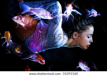 fantasy woman swimming with fishes - stock photo
