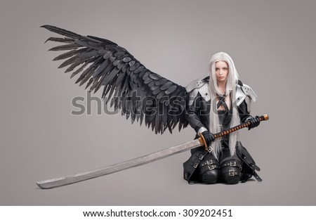 Fantasy woman warrior. Woman warrior with sword and wings isolated on the gray background - stock photo