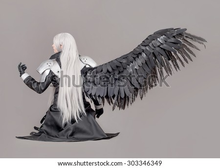 Fantasy woman warrior. Woman warrior with wings and armor isolated on the gray background - stock photo