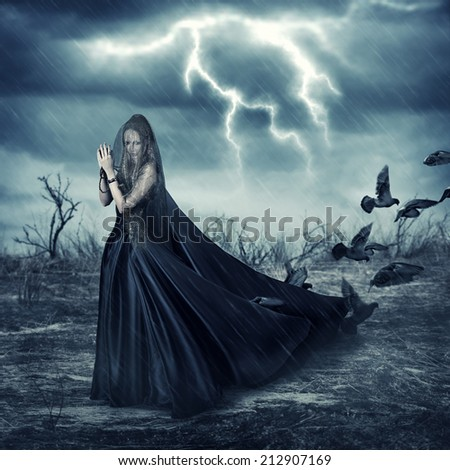 Fantasy world - beautiful woman in black fashionable medieval dress and pigeon birds
