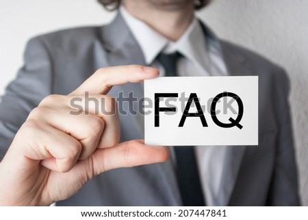 FAQ. Businessman in suit with a black tie showing or holding business card - stock photo