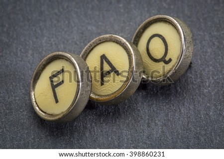 FAQ (frequently asked questions) acronym in old round typewriter keys against gray slate stone
