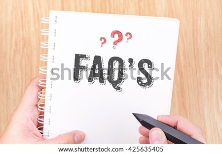 FAQ's word on white ring binder notebook with hand holding pencil on wood table,Business concept. - stock photo