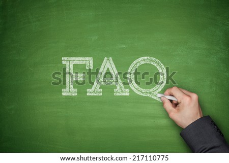 FAQ text concept on green blackboard with hand - stock photo