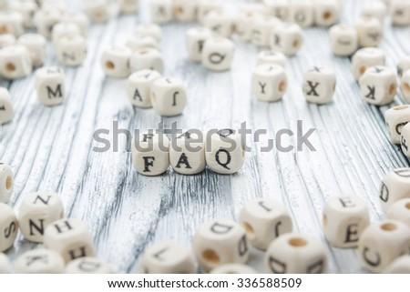 FAQ word written on wood block. - stock photo