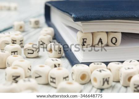 FAQ word written on wood block - stock photo