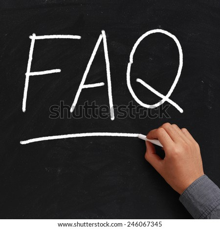 FAQ written on black chalkboard with white chalk in hand. - stock photo