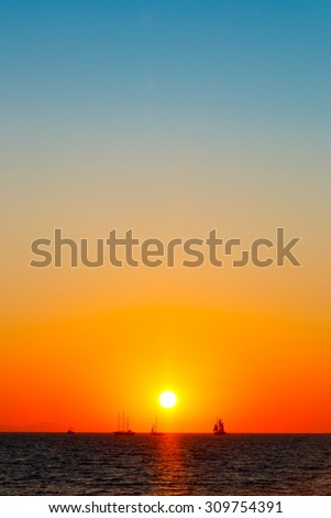 Far away ships on the sea in colorful sunset - stock photo